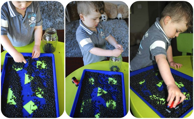 child playing with trains and filling and pouring with bean sensory tray