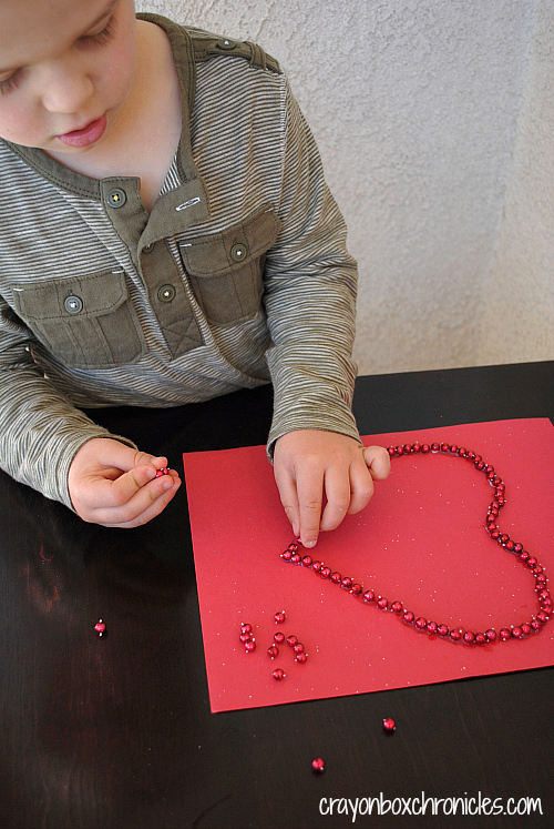 Child glueing red loose parts onto heart