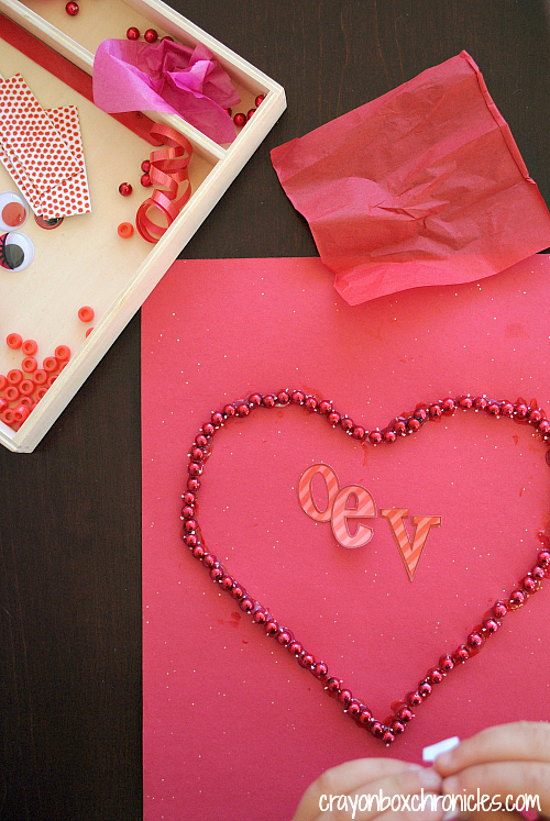 Beads glued around outline of heart with letters LOVE