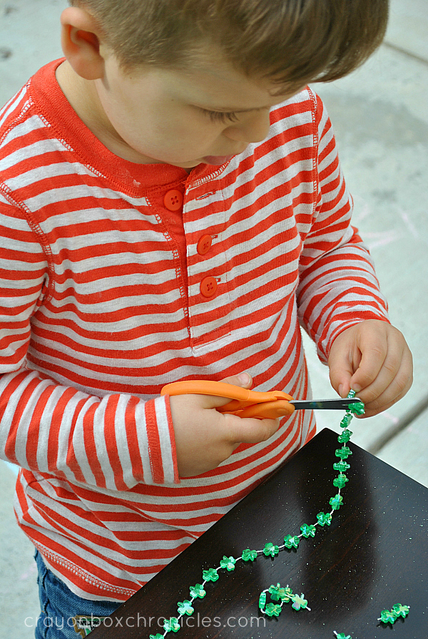 child cutting shamrock necklace