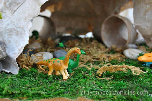 Dinosaurs playing in paper mache cave