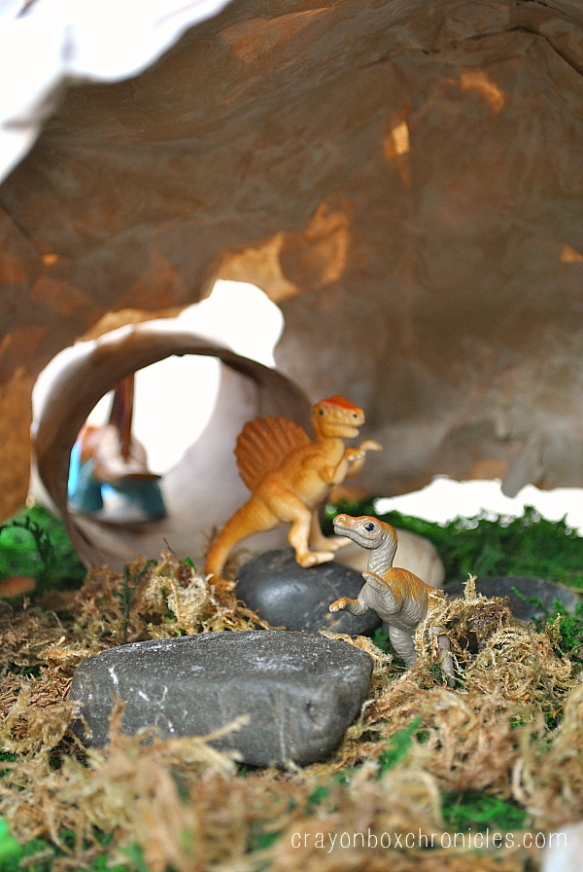 dinos on rocks inside paper mache cave