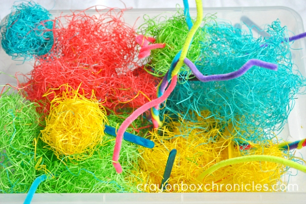 colored hay sensory bin with pipe cleaners and pop sticks