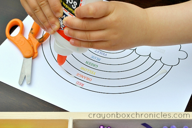 child adding glue to rainbow sensory collage