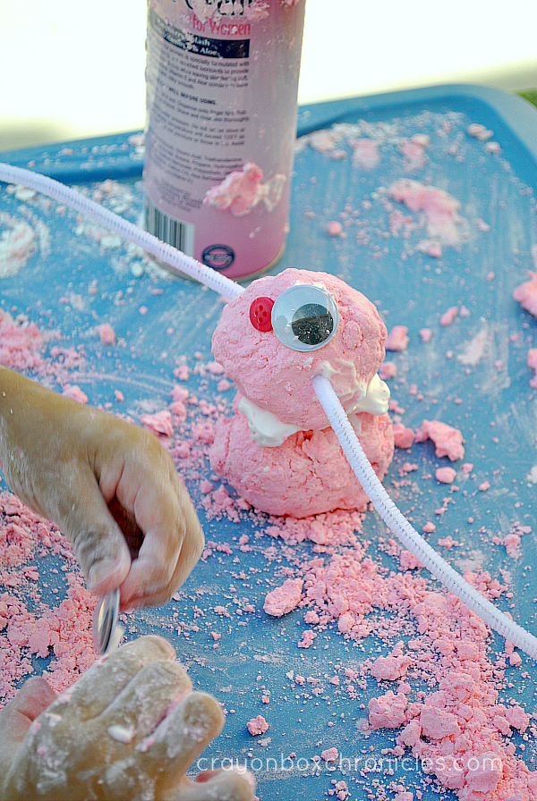 Child adding google eyes to raspberry foam dough bunny